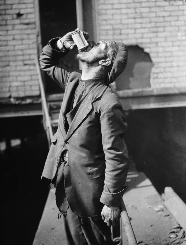 17th April 1936: A miner at Rose Heyworth colliery in South Wales drinking a can of beer to celebrate the wedding of R D Firth, the son of the mine owner, Sir William Firth. (Photo by Richards/Fox Photos/Getty Images)