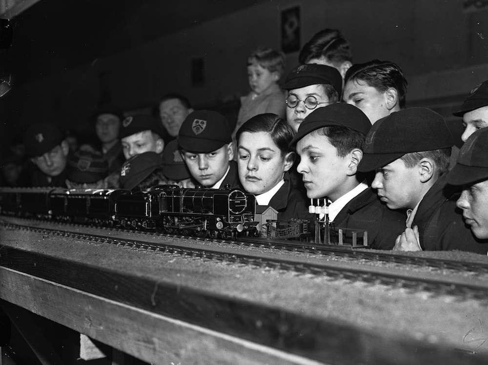 26th December 1936: Schoolboys gathered around a Royal Mail model train set at an exhibition organised by the Post Office at the Imperial Institute, South Kensington. (Photo by Harry Todd/Fox Photos/Getty Images)
