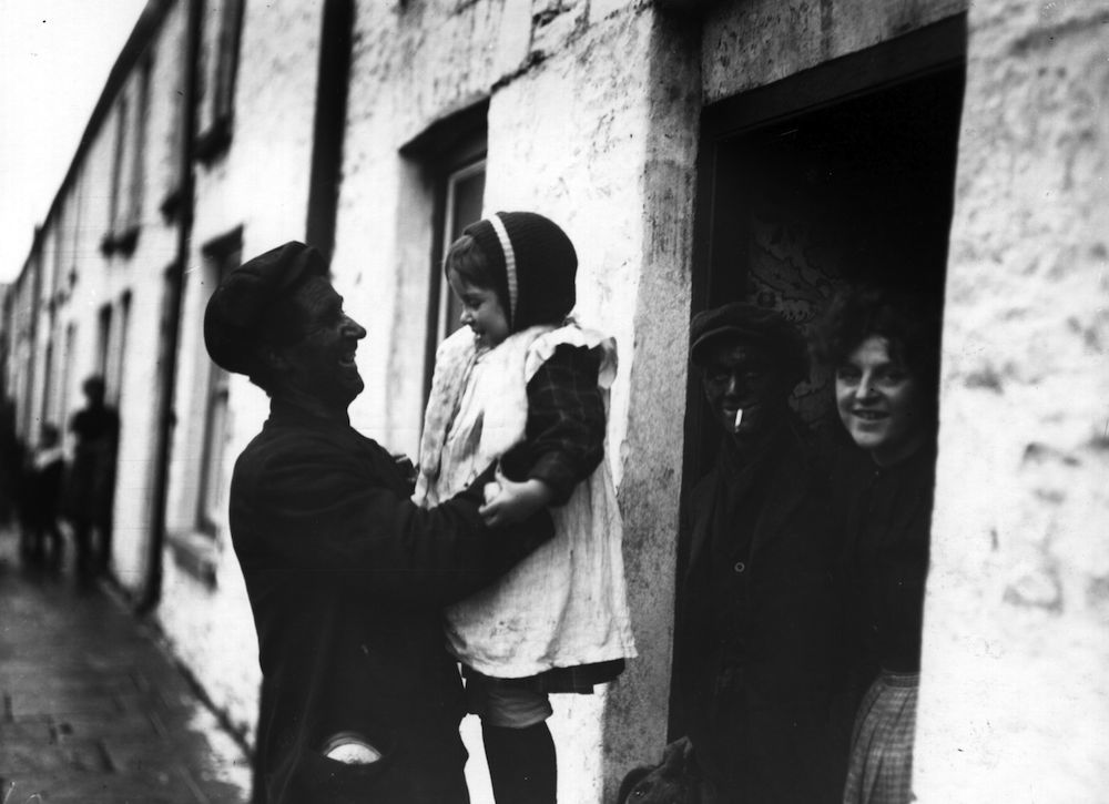 February 1912: A miner lifts up his daughter as he returns home from work at a pit in Wigan, during the coal strike crisis. (Photo by Topical Press Agency/Getty Images)