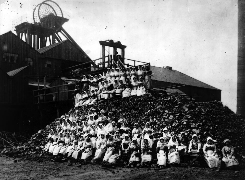 February 1912: Women mine workers sitting on a pile of coal during the coal strike in Wigan. (Photo by Hulton Archive/Getty Images)