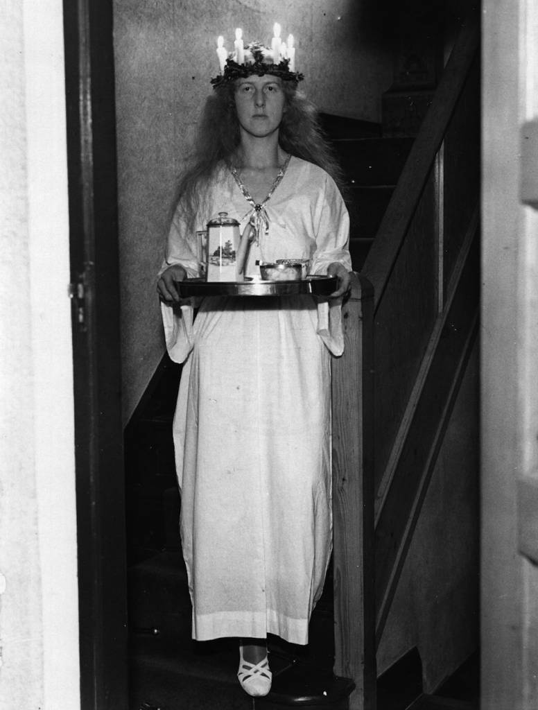 26th December 1936: A Swedish girl with her traditional Christmas candle headdress, carrying a tray of tea things. (Photo by Harry Todd/Fox Photos/Getty Images)