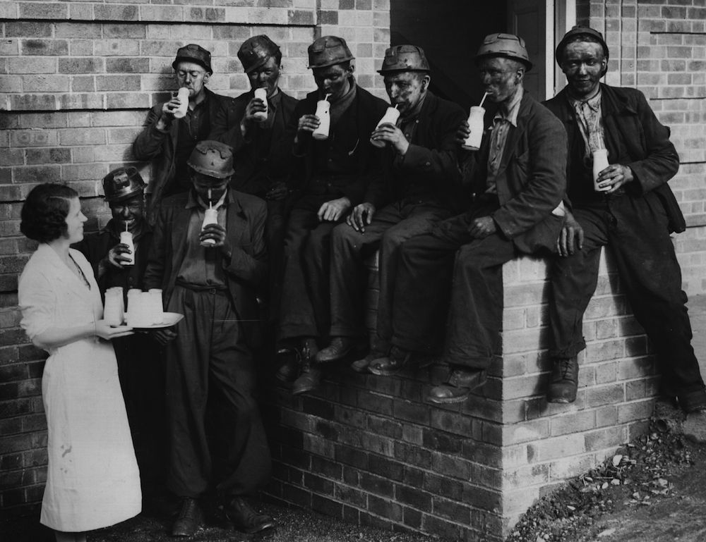 11th October 1938:  Miners, straight from the pit, taking their milk break in the sunshine at a new milk bar opened at Penallfe colliery.  (Photo by Fox Photos/Getty Images)