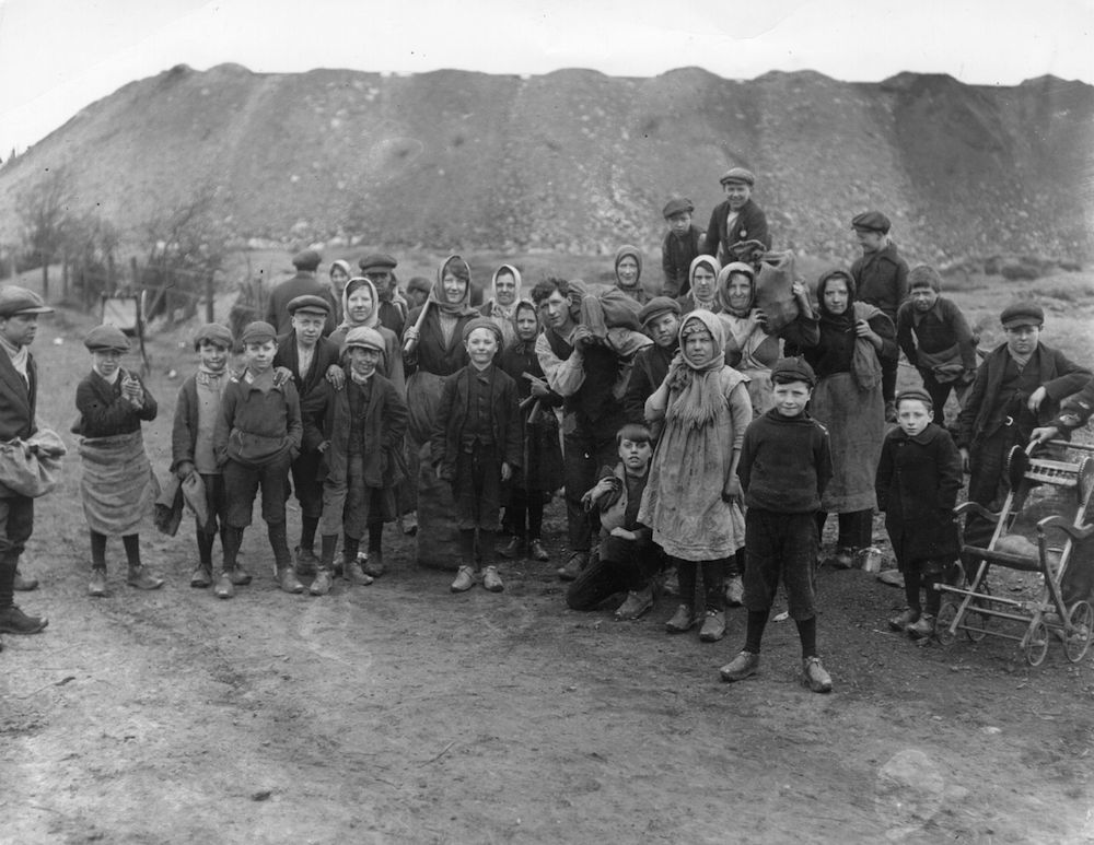 January 1921: Children, wearing clogs, gathering coal during the coal stike. (Photo by Topical Press Agency/Getty Images)