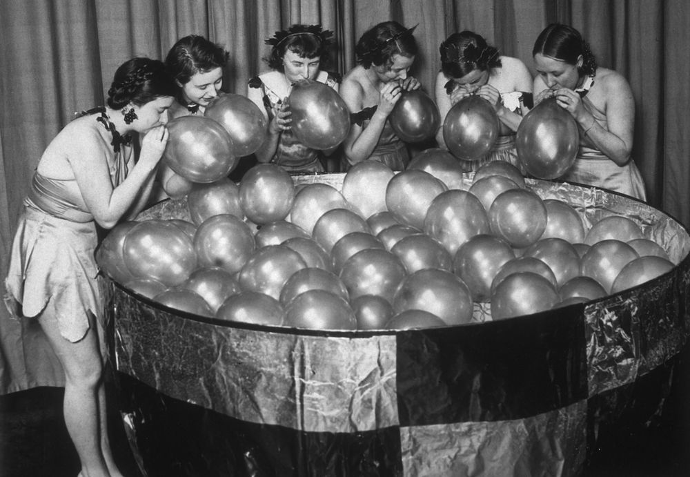 4th January 1933: Students from Clapham School of Art blowing up balloons for their giant glass of 'bubbly', which formed one of the attractions at the Chelsea Arts Ball at the Royal Albert Hall, London. (Photo by Fox Photos/Getty Images)