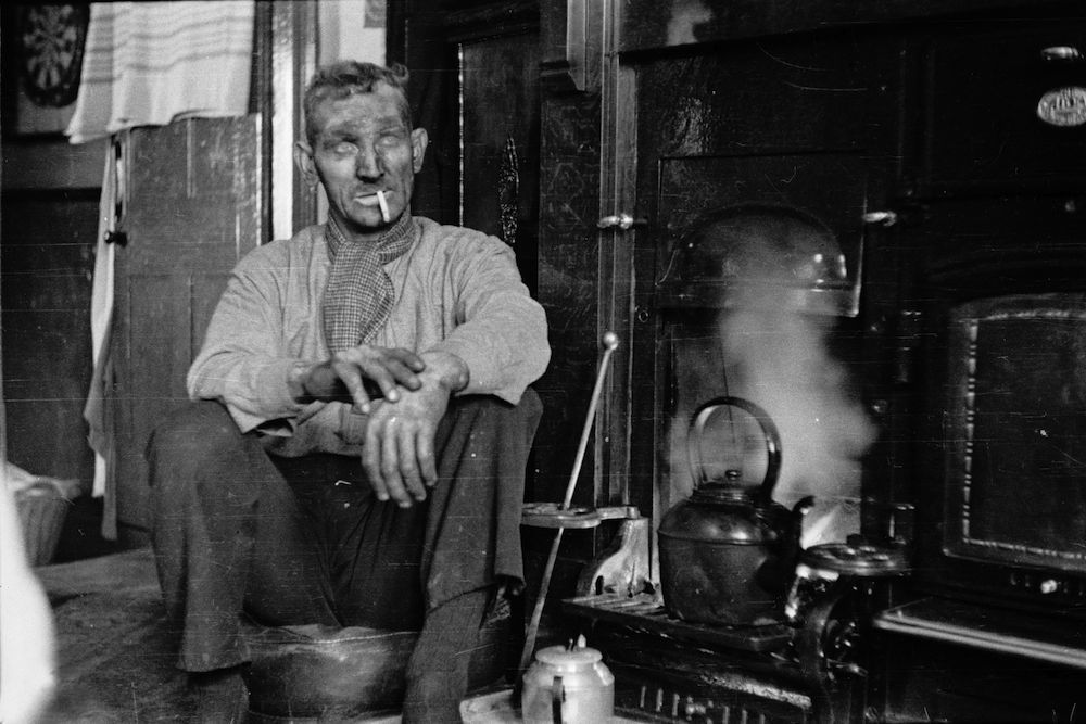 18th February 1939:  British coal miner Tommy Shotton relaxing with a cigarette after work.   (Picture Post - Coal Miner - pub. 1939)  (Photo by Topical Press Agency/Getty Images)