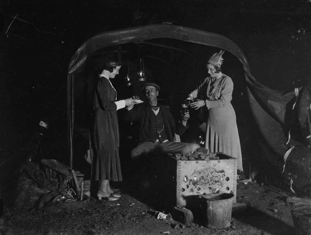 26th December 1932: Two Christmas revellers keeping the night watchman supplied with Christmas cheer. (Photo by Hudson/Topical Press Agency/Getty Images)