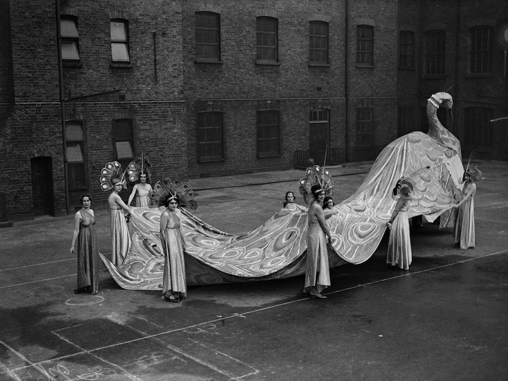 December 1929: Figure of a peacock with its tail as a train which is being held by attendants at a Chelsea Arts Ball rehearsal. (Photo by Fox Photos/Getty Images)