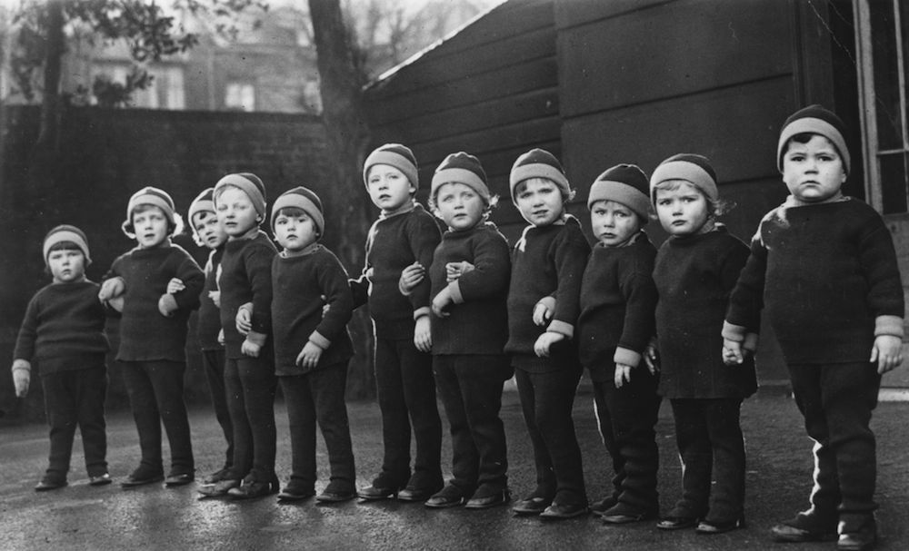 26th December 1933: A line of children wearing identical new woollen trousers, jumpers and hats at Leytonstone Children's home, London. (Photo by Fox Photos/Getty Images)