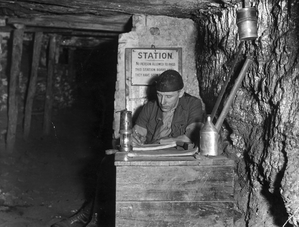 18th October 1934: In a Durham coal mine a deputy makes out his report at the 'kist' or station after inspecting the coal face to see all is safe before a shift starts. A miner's lamp is beside him. (Photo by David Savill/Topical Press Agency/Getty Images)