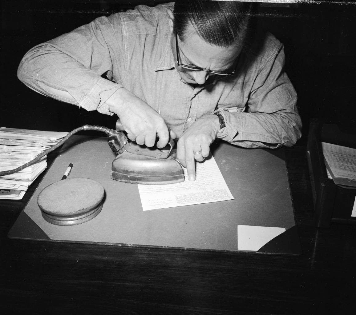 circa 1958: William Abel, mail censor at Iowa's State Prison, Fort Madison, using a hot iron to bring out a secret message written in lemon juice on a letter. A liquor smuggling plot was consequently foiled. Bill estimates he has read 500,000 letters since starting his job four years ago. (Photo by Three Lions/Getty Images)