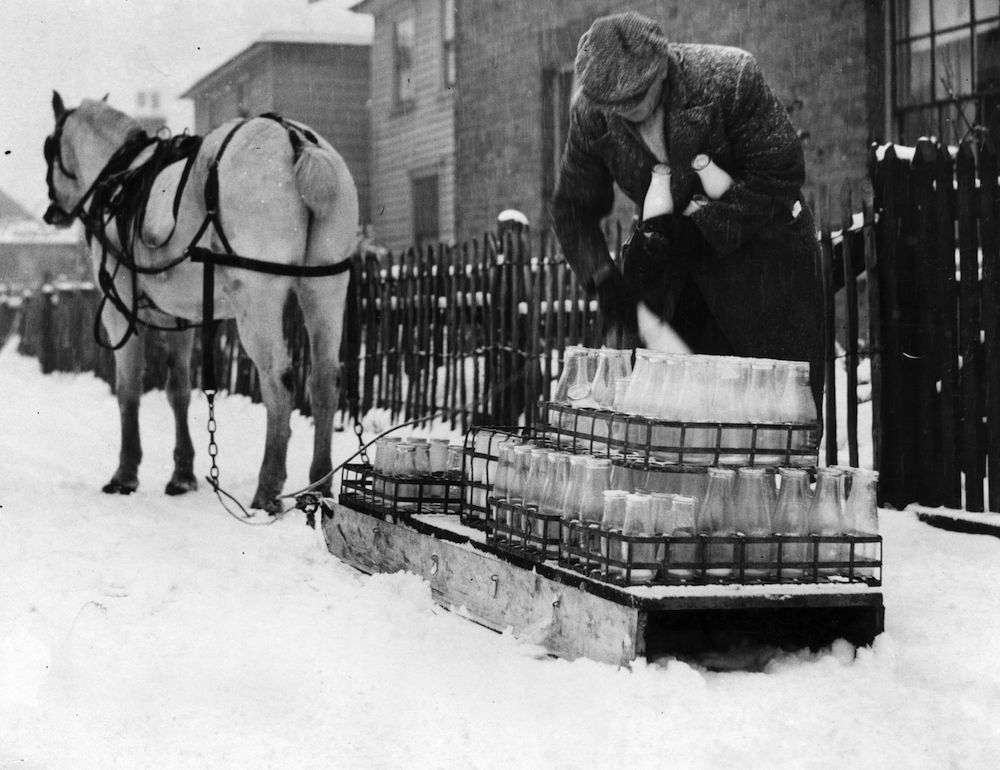 26th December 1938: A milkman in Loughton, Essex, delivering milk on a sledge drawn by a pony. (Photo by Norman Smith/Fox Photos/Getty Images)