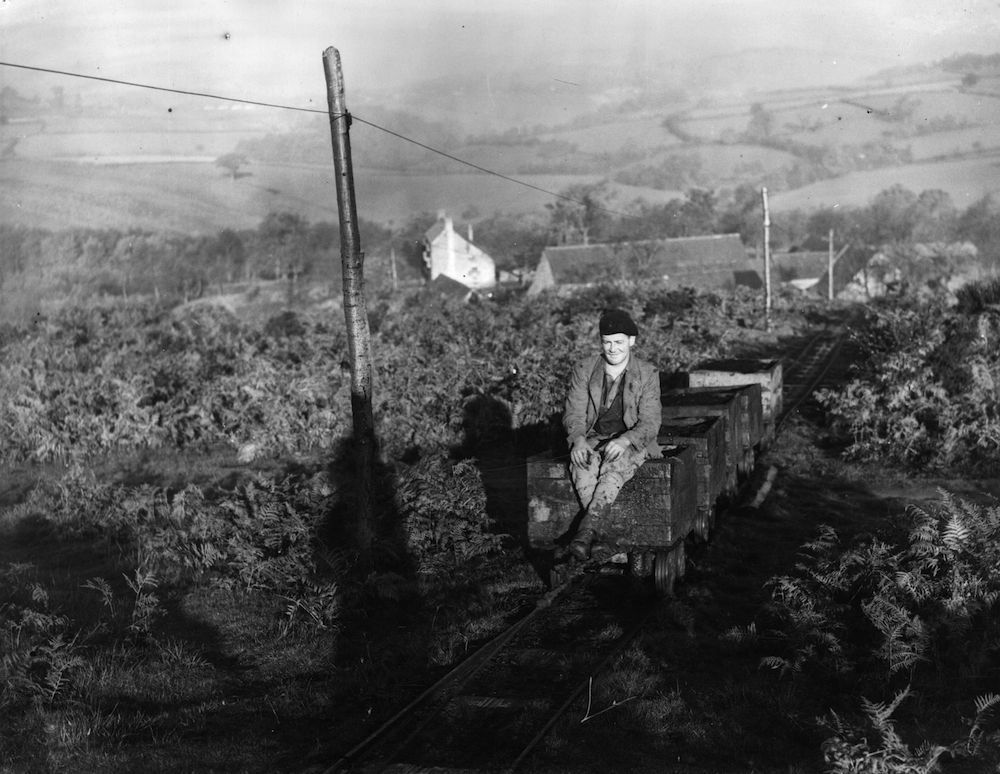 18th November 1941:  A 'Freeminer' hitches a ride on a coal rail truck through the bracken and trees to the road. A 'Freeminer' is the term given to those who have the right to mine for coal in some of the small mines in the Forest of Dean. Every ounce of coal that can be mined is vital to the war effort.  (Photo by Maeers/Fox Photos/Getty Images)