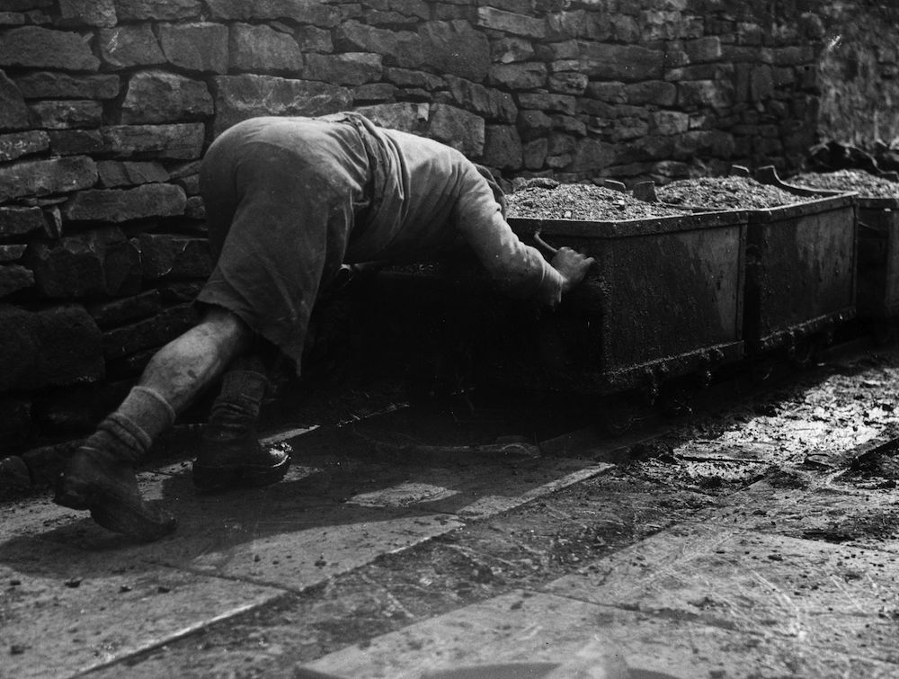 28th April 1936: A miner pushing a coal truck at the Old Meadows coal pit, Bacup, Lancashire. (Photo by Fox Photos/Getty Images)