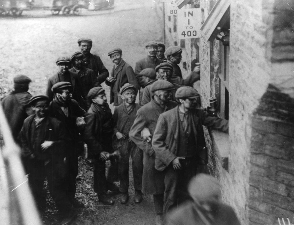 circa 1920: A group of miners receiving their wages after finishing a shift in the coal mine. (Photo by Hulton Archive/Getty Images)