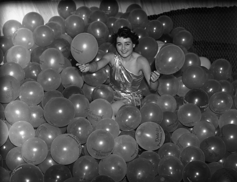 31st December 1937: Joanna Brandon surrounded by balloons which are to be released at midnight from the roof of the Albert Hall during the Chelsea Arts Ball. The balloons are marked with the name Dolcis, a shoe company. (Photo by A. Hudson/Topical Press Agency/Getty Images)