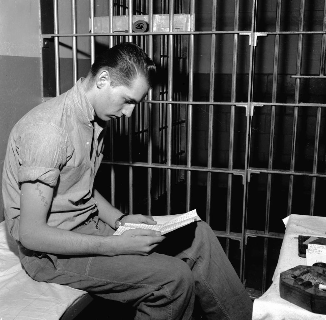 circa 1955: Warren Jack Nutter, sentenced to hang for murdering an Iowa policeman, reading a letter from his mother in his cell in the Iowa State Penitentiary at Fort Madison. (Photo by Evans/Three Lions/Getty Images)