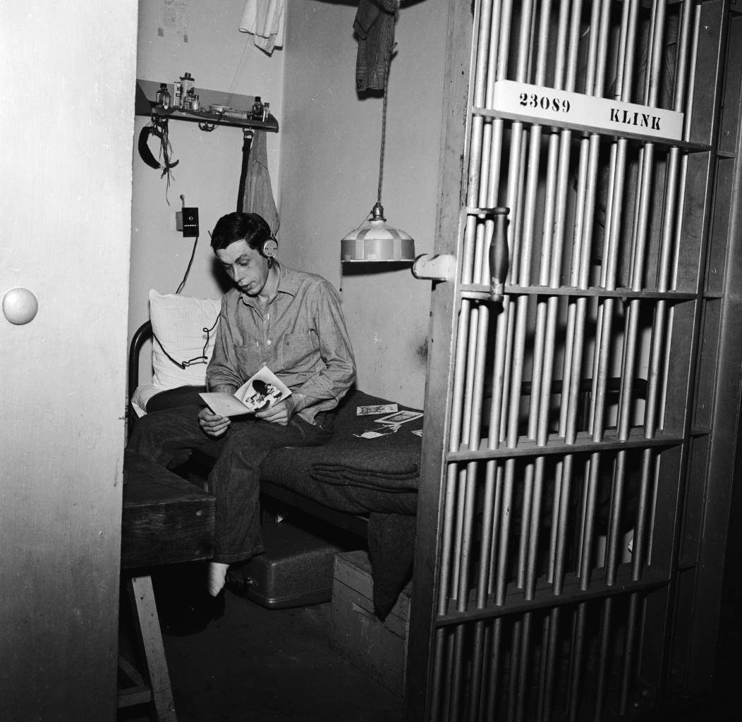 circa 1955: A prisoner at the Iowa State Penitentiary in Fort Madison reading his Christmas cards in his cell. (Photo by Vandermyn/Three Lions/Getty Images)