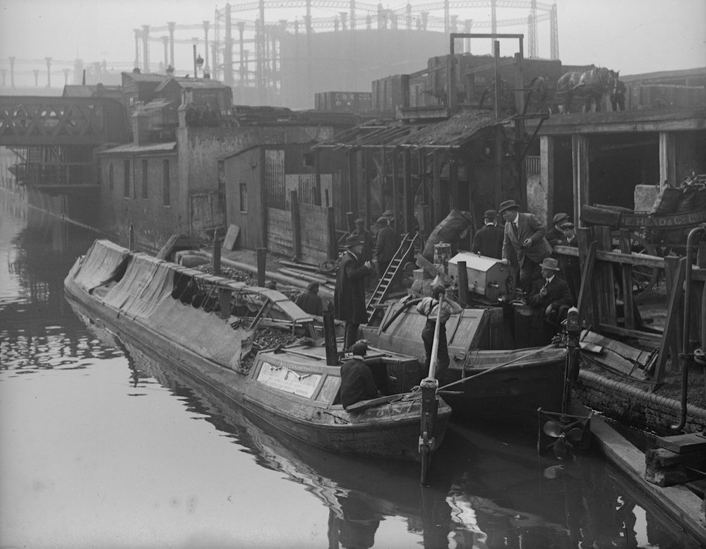 25th April 1917: A motor coal barge on Regent's Canal unloading its cargo. (Photo by Topical Press Agency/Getty Images)