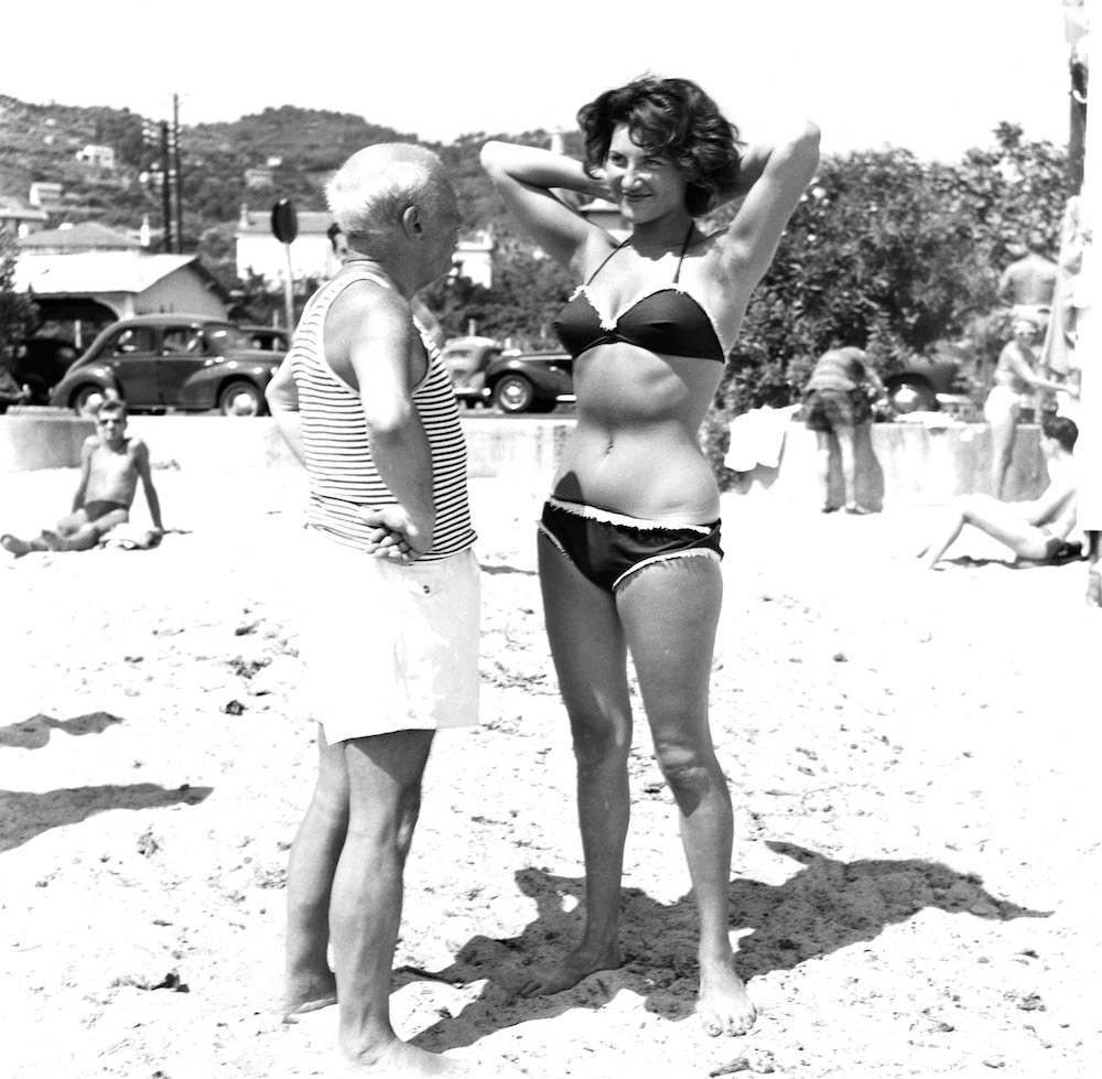 Spanish painter Pablo Picasso (1881 - 1973) makes a young woman wearing a bikini smile on the beach at Golfe Juan on the Riviera, Vallauris, France, 1960s. (Photo by Hulton Archive/Getty Images)