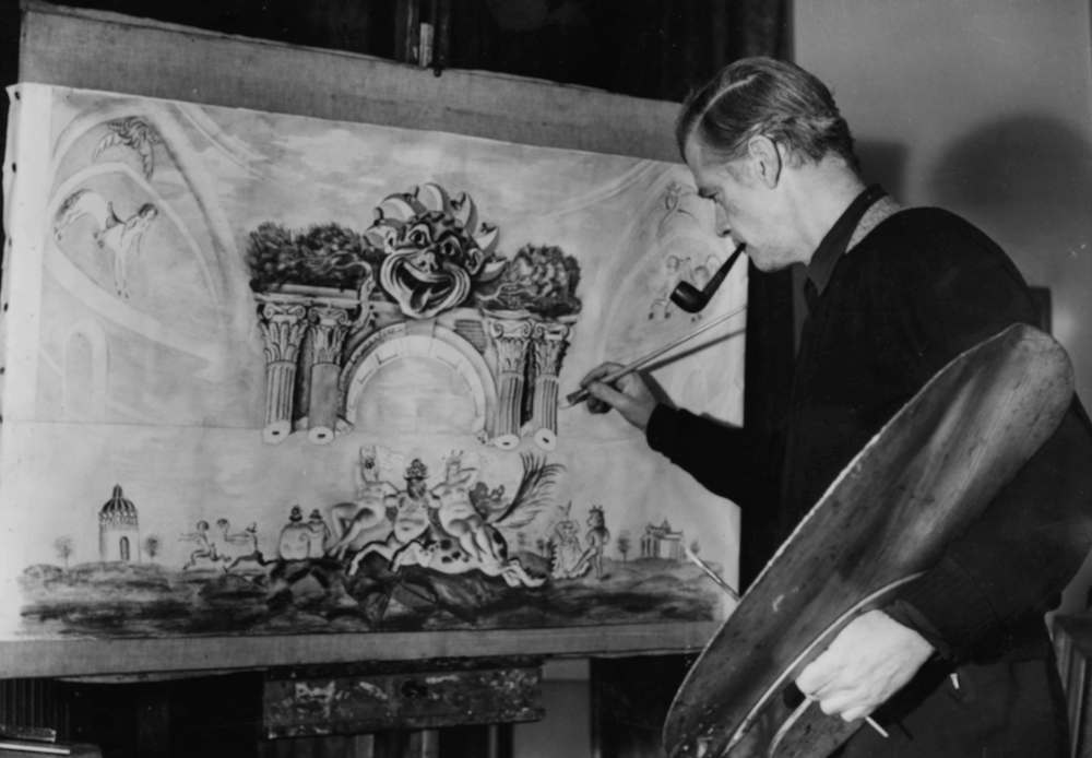 English artist Alfred Thomson smoking a pipe as he paints a panorama of the Chelsea Arts Ball at Royal Albert Hall, circa 1950. (Photo by Fox Photos/Hulton Archive/Getty Images)