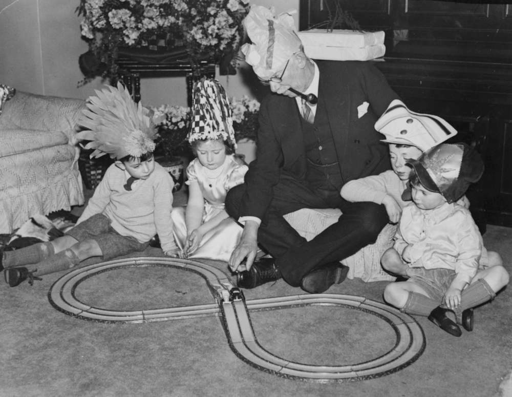 British trade unionist and Labour Party politician James Henry Thomas, pictured with his grandchildren playing with a model railway, at home in Victoria, London, December 26th 1935. (Photo by Horace Abrahams/Keystone/Getty Images)
