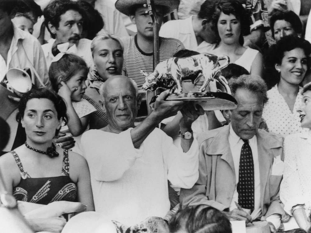 Spanish-born artist Pablo Picasso (1881 - 1973) holds up a statuette of a fighting bull, presented to him by toreadors in appreciation of his art, in the stands at a bullfight at Vallauris, France, 11th August 1955. On the left is Jacqueline Roque (1927 - 1986), who later married Picasso. On the right is French author, artist and filmmaker Jean Cocteau (1889 - 1963). (Photo by Keystone/Hulton Archive/Getty Images)