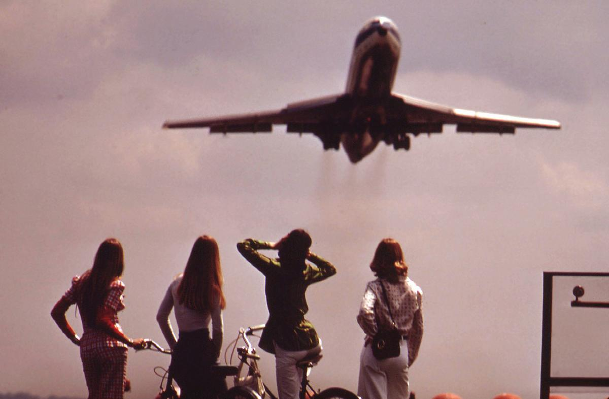 One of four bicyclists holds her ears against the roar of the jet taking off from National Airport in Washington, District of Columbia, in May of 1973. # John Neubauer:NARA