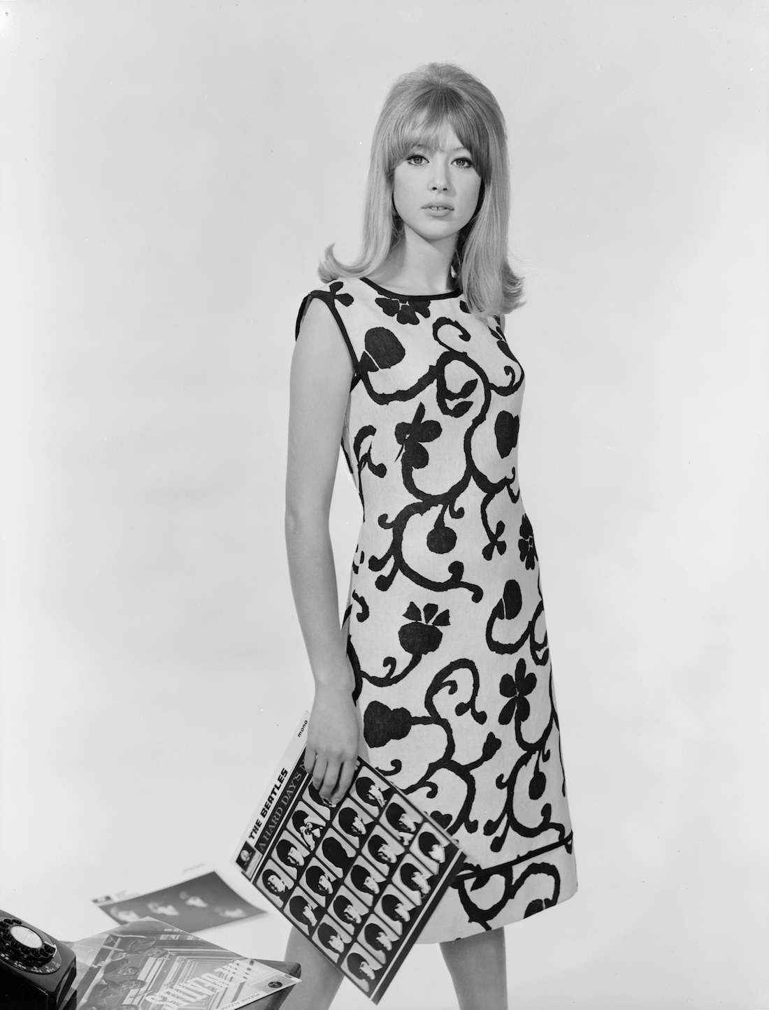 1964: Patti Boyd models a Brilkie sleeveless sheath dress with a large, stylised floral pattern. She is holding the Beatles album 'A Hard Day's Night'. (Photo by Chaloner Woods/Getty Images)