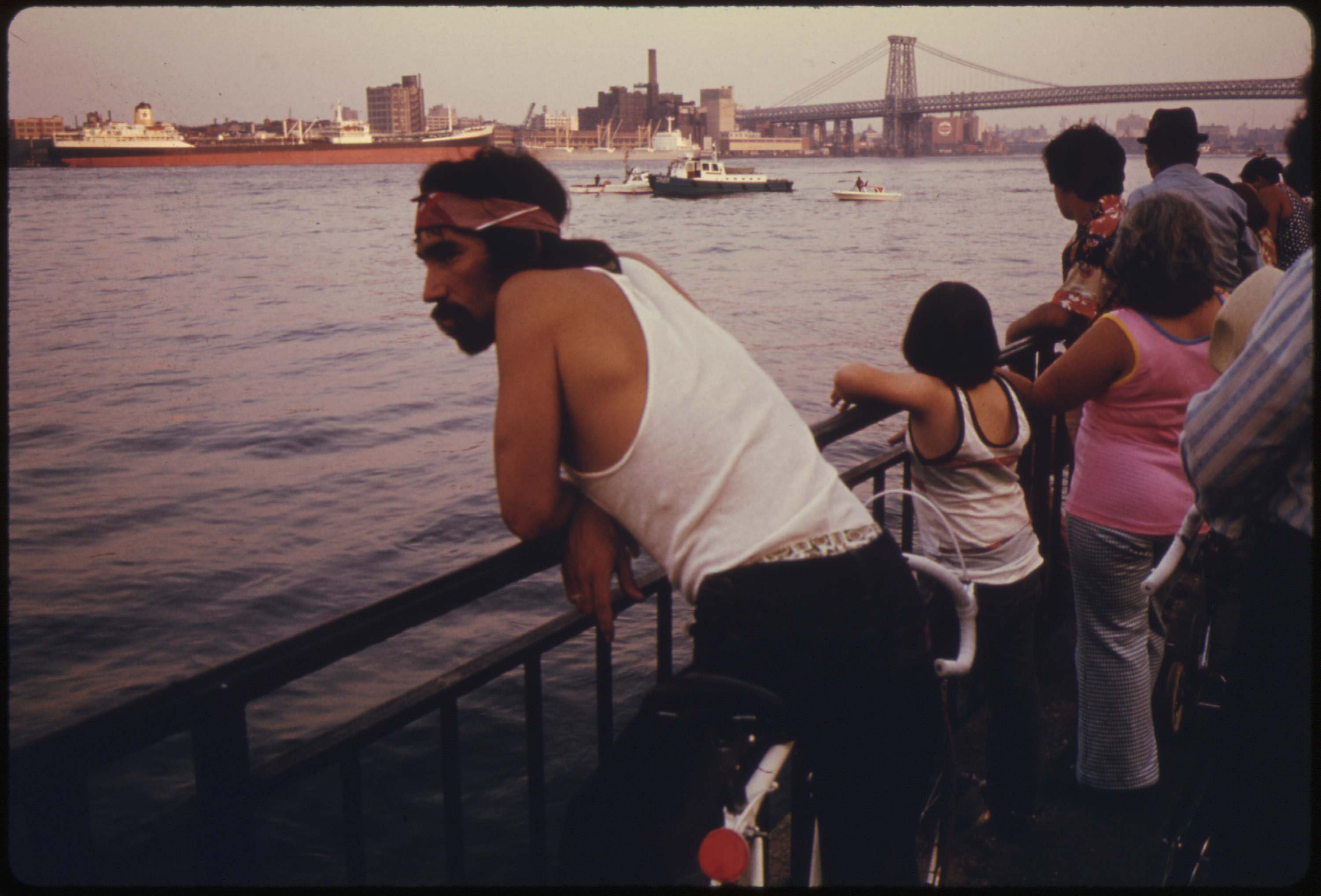 People looking at boat traffic on the East River with the Manhattan Bridge and NYC in the background, July 1974.Documerica: Danny Lyon's Photos of New York City in the Summer of 1974