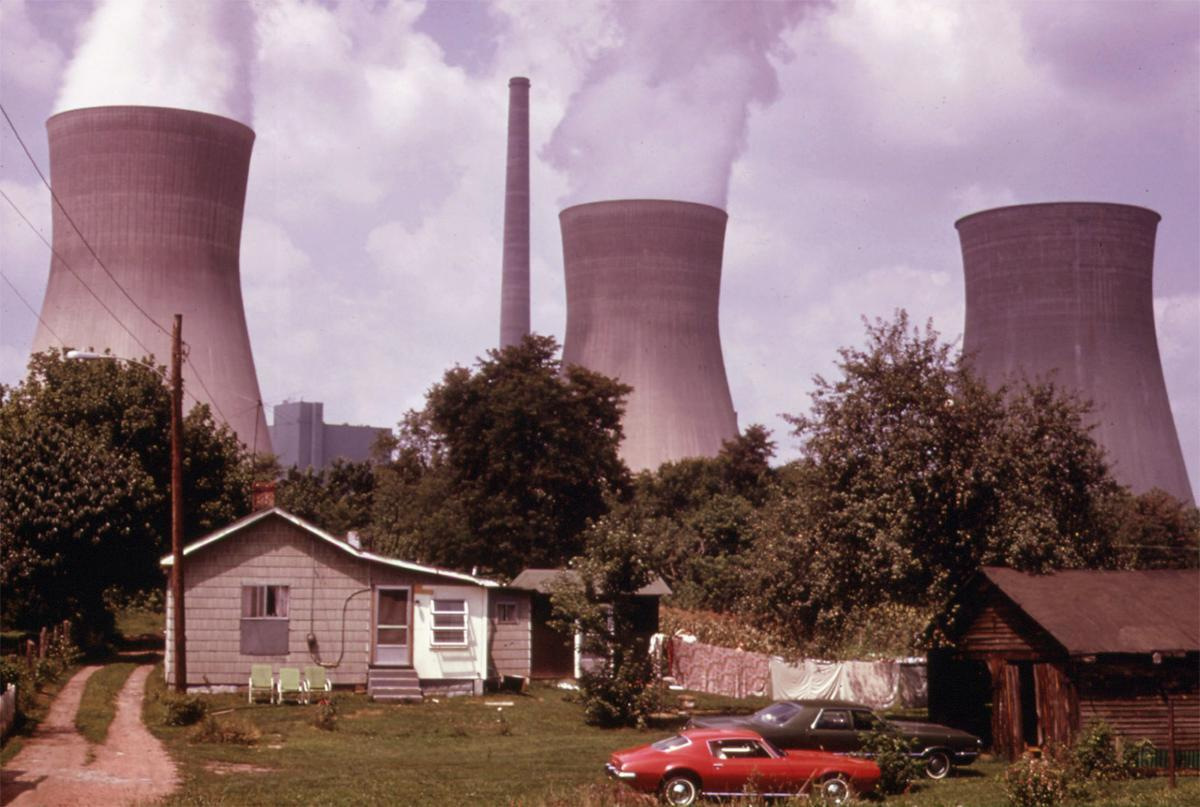 Water cooling towers of the John Amos Power Plant loom over a home located across the Kanawha River, near Poca, West Virginia, in August of 1973. # Harry Schaefer:NARA