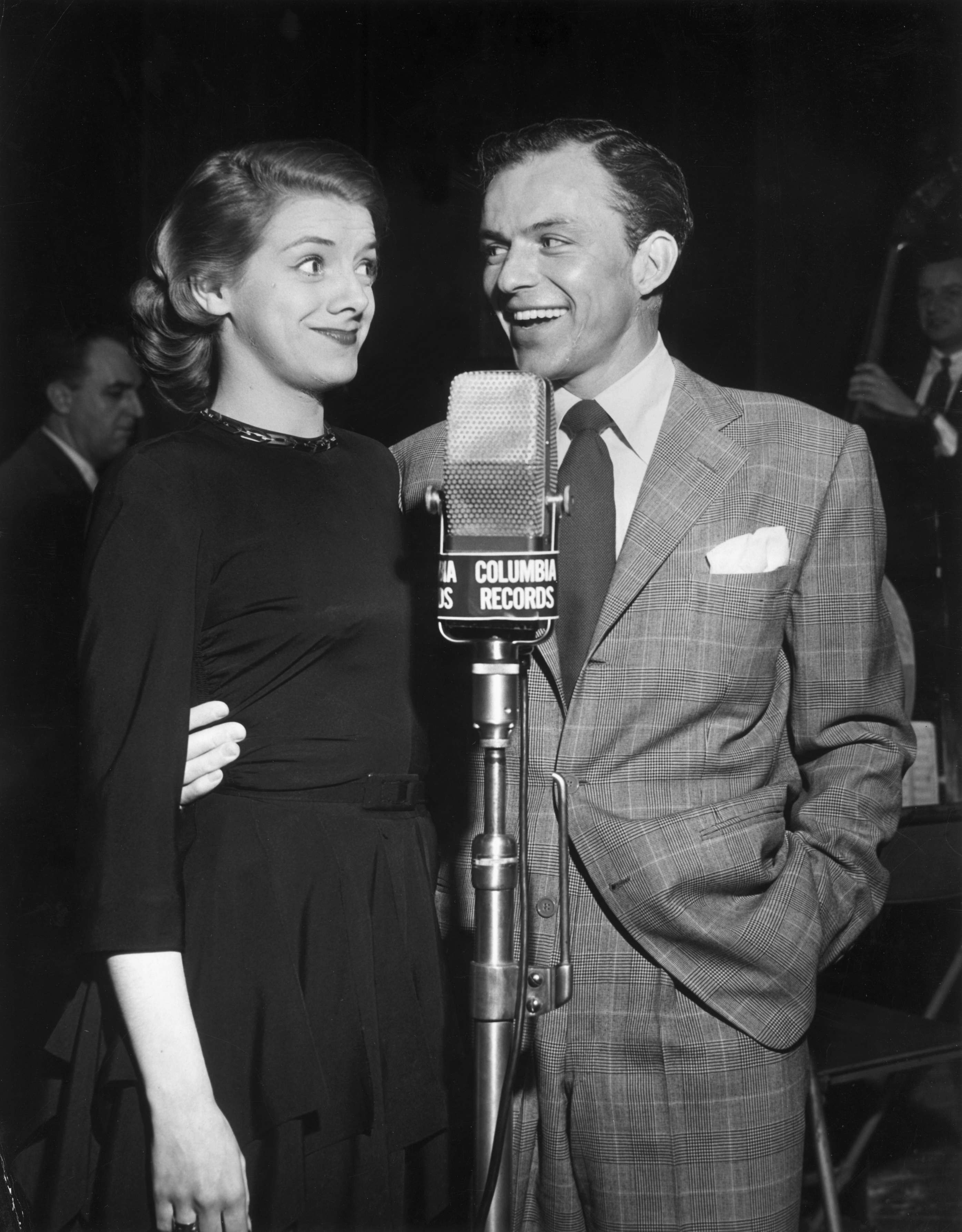 circa 1950: American actors and singers Rosemary Clooney (1928 - 2002) and Frank Sinatra stand together in front of a Columbia Records microphone. Sinatra is smiling and has his arm around Clooney. (Photo by Hulton Archive/Getty Images)