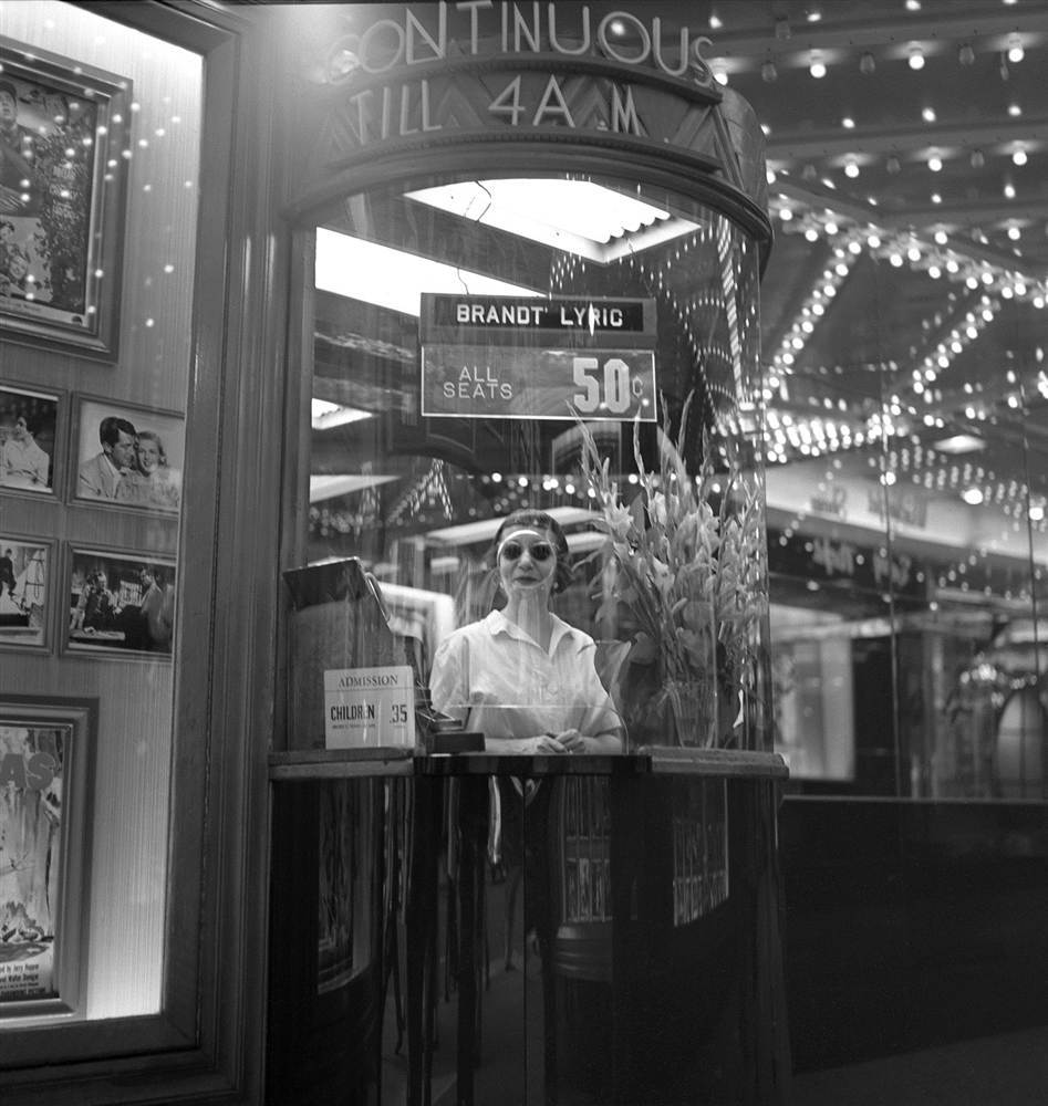 A woman peers out from a ticket booth of a movie theater in New York's Times Square in 1954.
