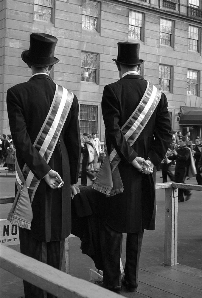 Two parade officials watch New York's Saint Patrick's Day parade pass by on Fifth Avenue as one of them sneaks a cigarette break.