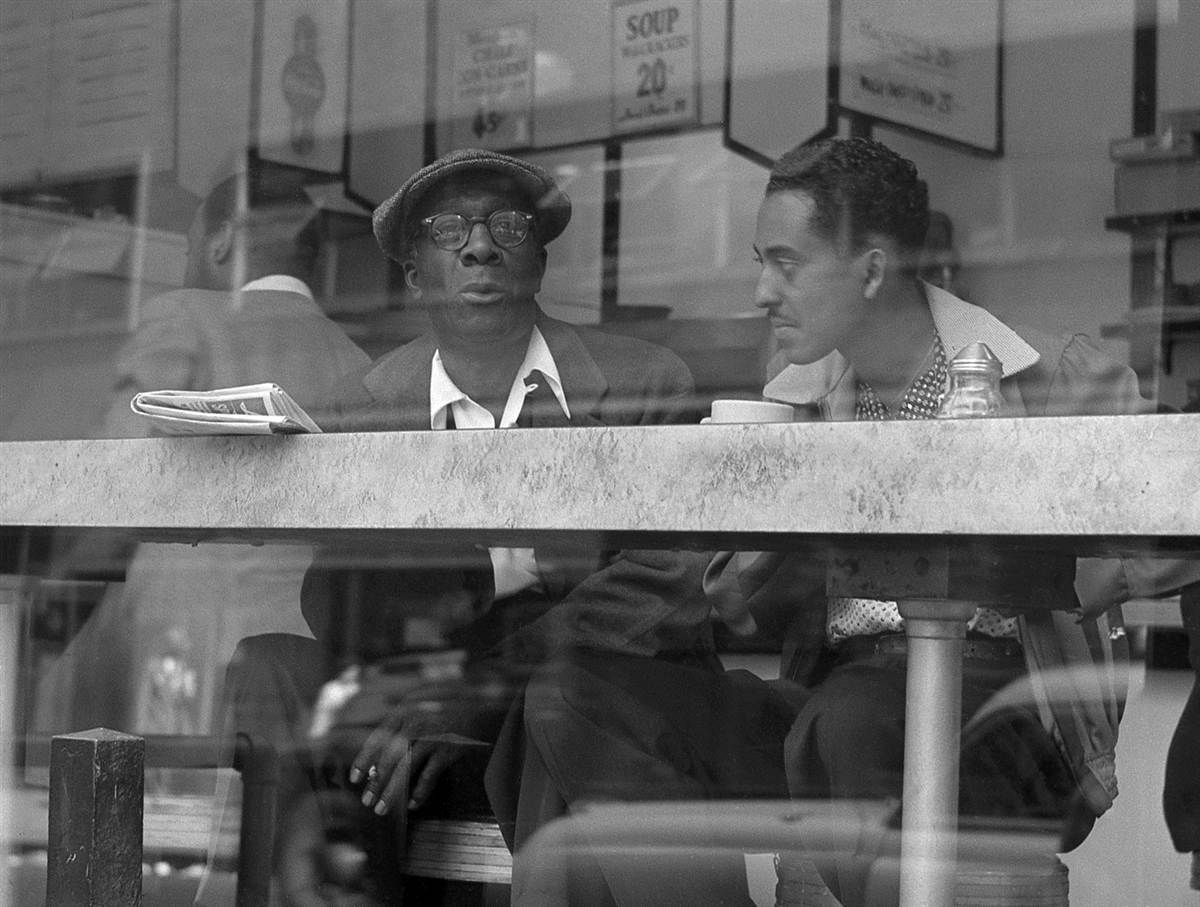 Two men chat in a coffee shop window near Times Square in April 1954.