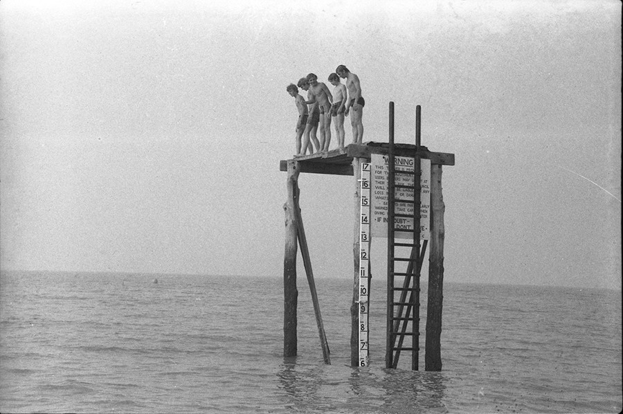 A black and white photograph by Reginald Alan Westaway of boys on the diving platform in Herne Bay in the mid-70s Read more: http://civilianglobal.com/gallery/property-of-a-gentleman/#ixzz3vA5HJmMC