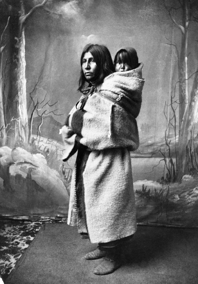 Blackfoot women with baby on her back. Date: [ca. 1886]