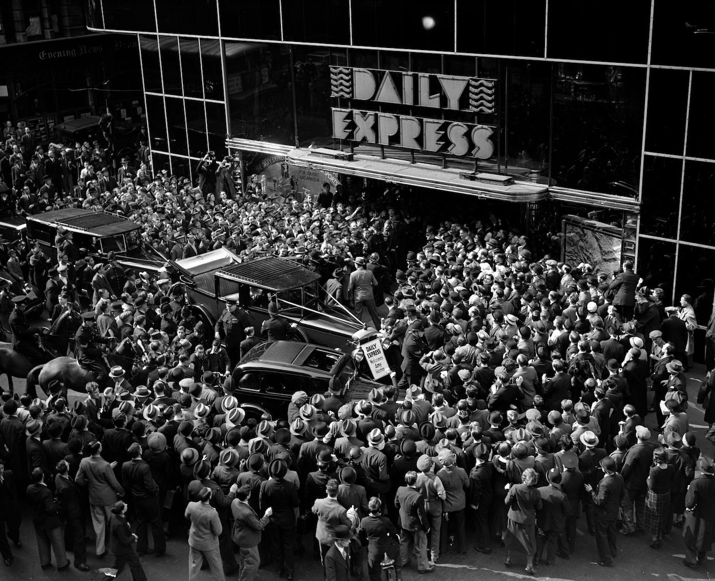 December 1932: Crowds gather round the entrance to the Daily Express building, Fleet Street, London, to greet English aviator Amy Johnson (1903 - 1941), after her record solo flight to Cape Town. (Photo by London Express/Getty Images)
