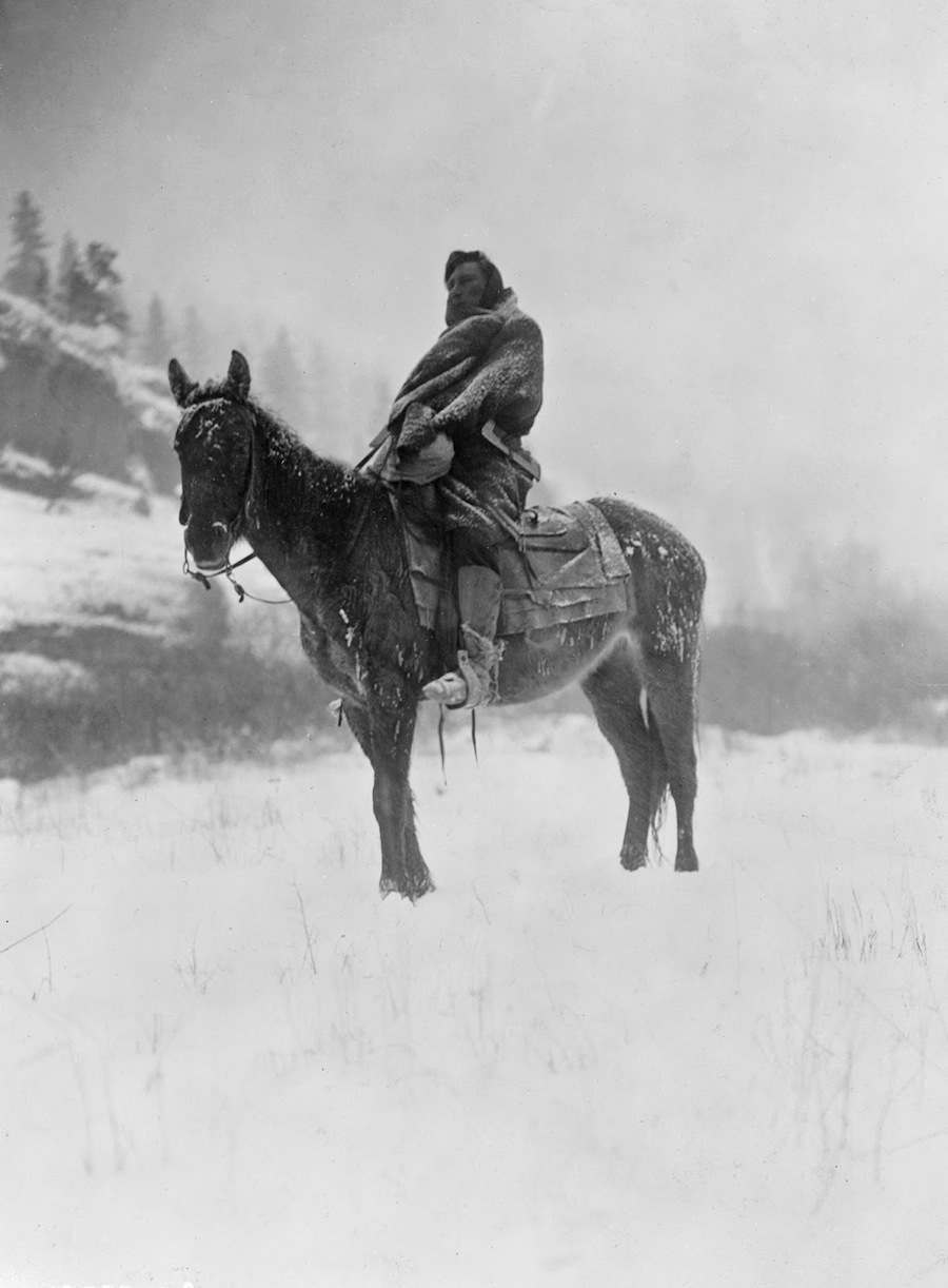 Edward S. Curtis - Apsaroke man on horseback on snow-covered ground, probably in Pryor Mountains, Montana