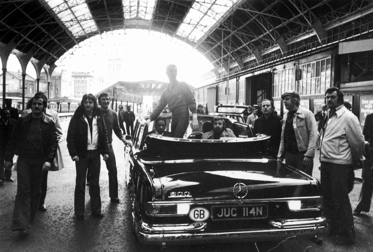 English singer David Bowie (centre) standing in a Mercedes convertible at Victoria Station, London, during his 'Station To Station' tour, 2nd May 1976. Moments after this picture was taken, Bowie made a controversial gesture, thought by some to be a Nazi salute. (Photo by Keystone/Hulton Archive/Getty Images)