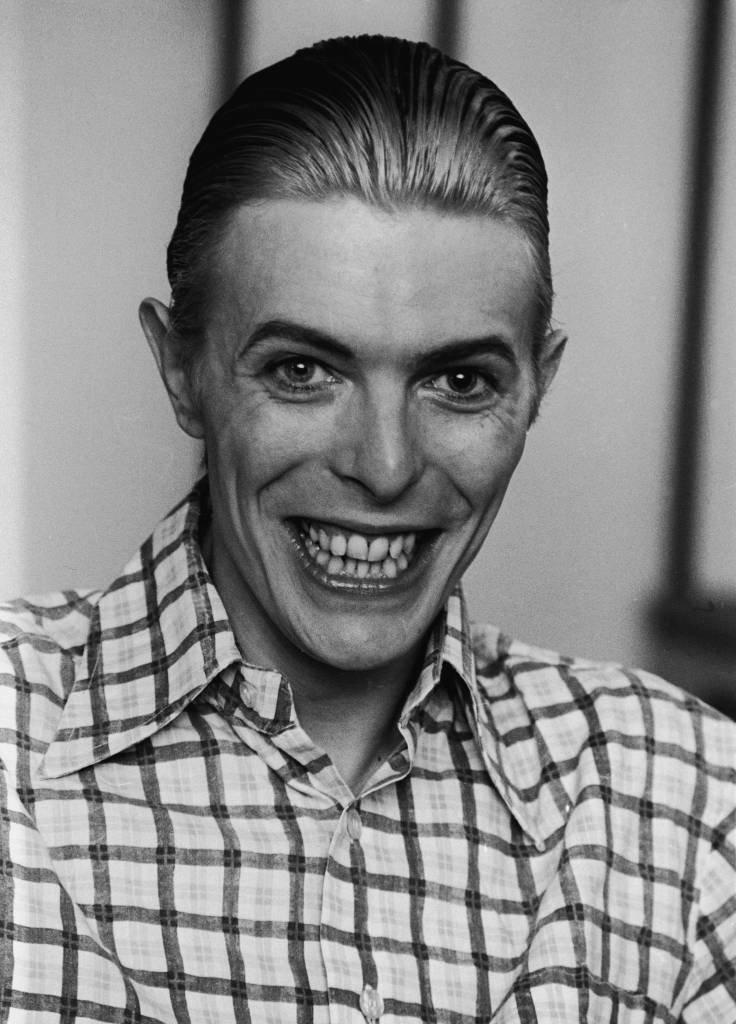 British rock singer and actor David Bowie grins broadly, wearing a plaid shirt with his hair slicked back, circa 1980. (Photo by Express Newspapers/Getty Images)