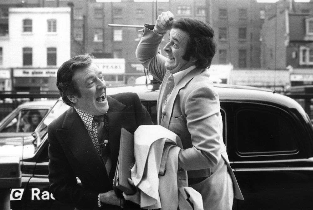 Terry Wogan, broadcaster and writer, cavorts with fellow broadcaster Eamonn Andrews (1922 - 1987). (Photo by Evening Standard/Getty Images)