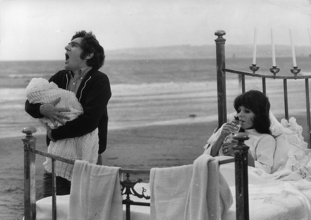 Anthony Newley tries to quieten the baby by singing as his wife Joan Collins enjoys a drink in bed which is set on a beach ! (Photo by Evening Standard/Getty Images)