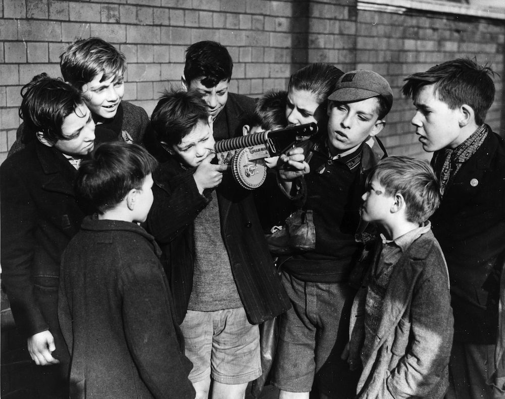 16th November 1937: A boy shows off his new toy to a group of envious friends. It is a replica of an American machine gun as used by gangsters and 'G ' men which releases a shower of sparks when the trigger is pulled. (Photo by Fox Photos/Getty Images)
