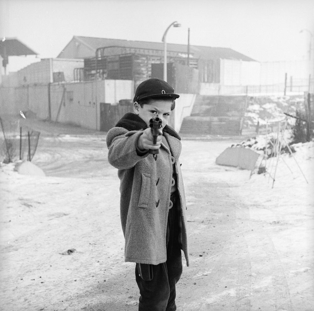 January 1958: A young boy looks down the sights of a revolver. (Photo by R. Mathews/BIPs/Getty Images)