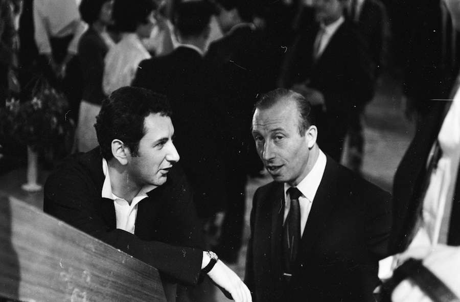 18th July 1962: British film director Michael Winner (left) in conversation with producer Harold Baim during the filming of 'The Cool Mikado'. (Photo by Terry Fincher/Express/Getty Images)