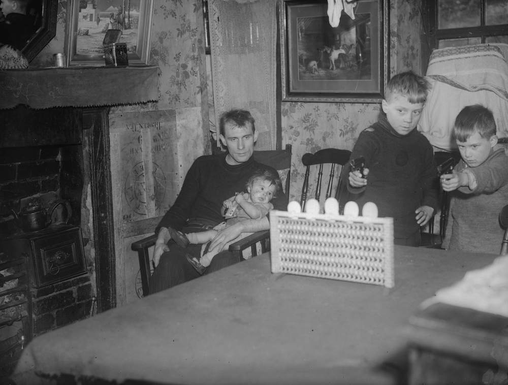 17th December 1934: A family living in one of the two bedroom hovels in Ebbw Vale, South Wales. A family of seven was found living in one of these rooms, and many such houses have subsequently been condemned as unsanitary. (Photo by Richards/Fox Photos/Getty Images)