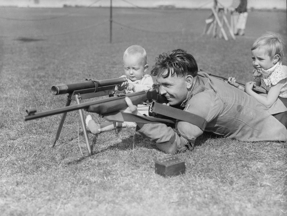 13th September 1935: A competitor at a Society of Miniature Rifle Clubs meeting in Margate, Kent has the assistance of his young daughter and 12 month old son. (Photo by Fred Morley/Fox Photos/Getty Images)