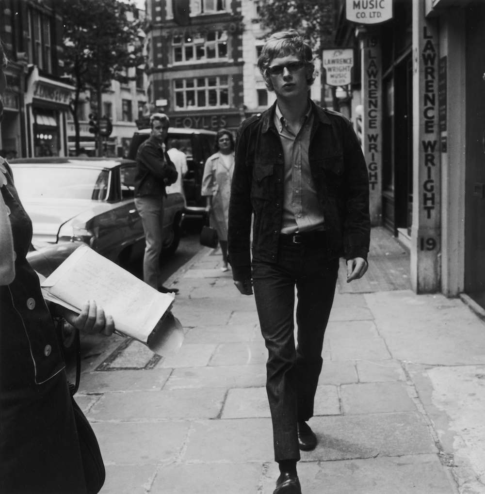10th August 1964: British music executive Andrew Loog Oldham, manager and promoter of The Rolling Stones in Denmark Street, London, popularly known as Tin Pan Alley. (Photo by Richard Chowen/Evening Standard/Getty Images)