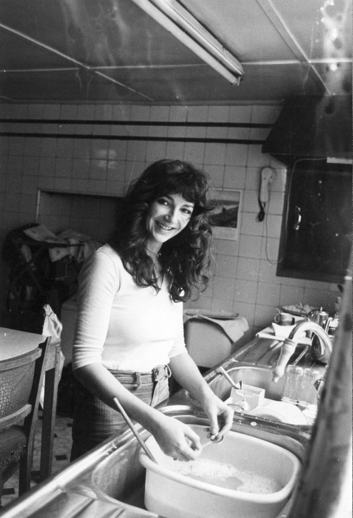 English singer-songwriter and musician Kate Bush doing the washing up at her family's home in East Wickham, London, 26th September 1978. (Photo by Chris Moorhouse/Evening Standard/Hulton Archive/Getty Images)