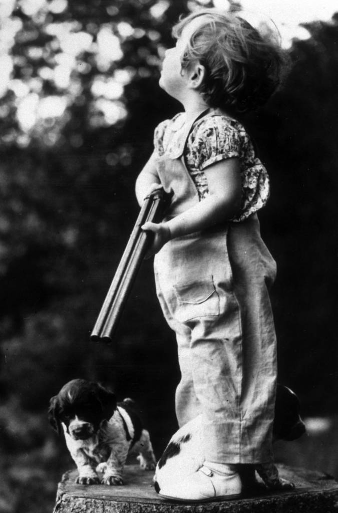 circa 1938: A young hunter looking expectantly into the trees, while her two dogs wait at her feet. (Photo by Fox Photos/Getty Images)